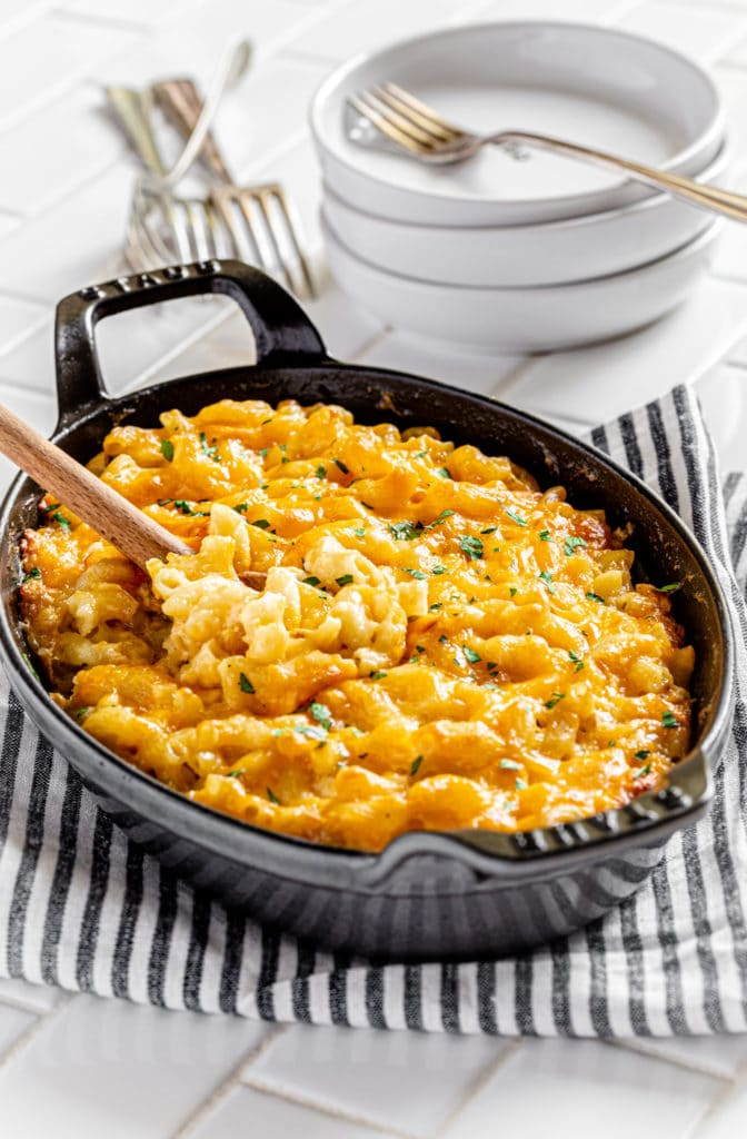 Southern Baked Mac and Cheese in an oval Staub baker with a wooden spoon.