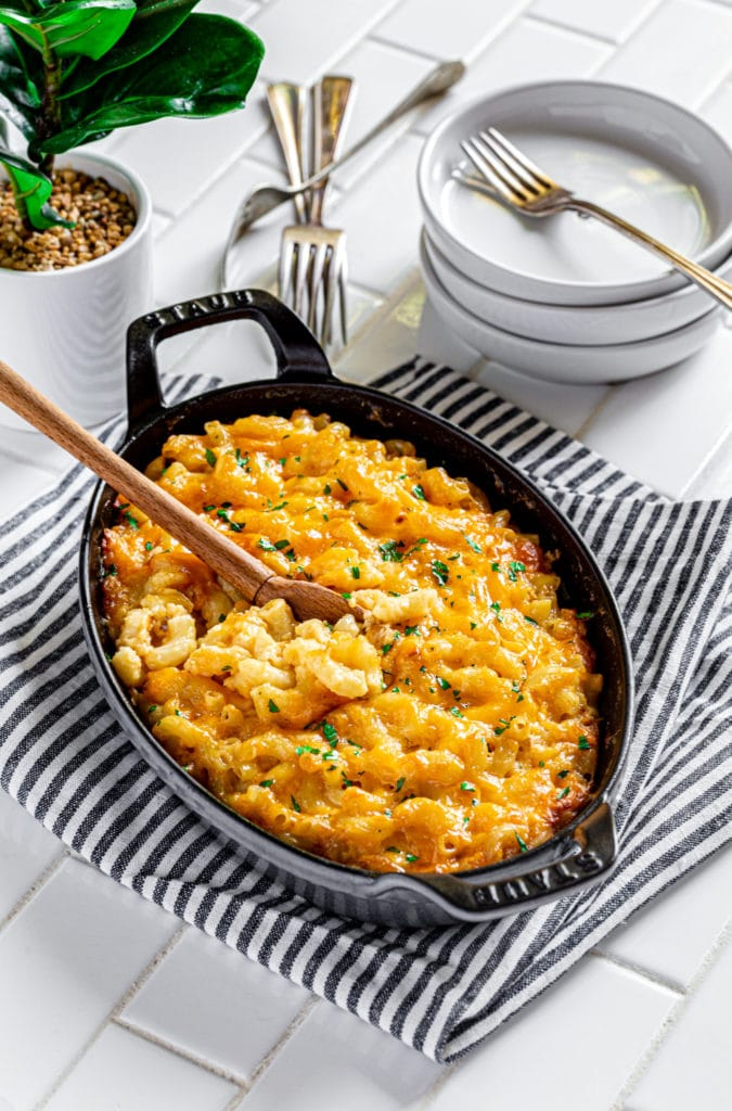 Baked mac and cheese in a Staub oval baker in graphite grey on a white-tile counter.