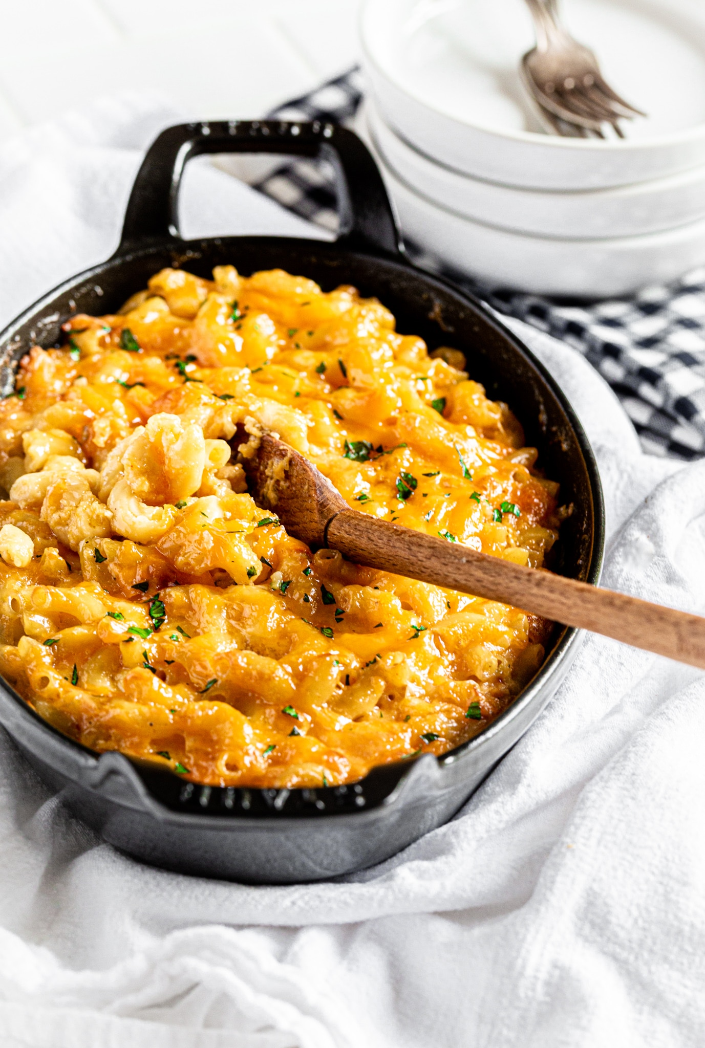 A graphite Staub gratin dish with baked macaroni and cheese on a white countertop.
