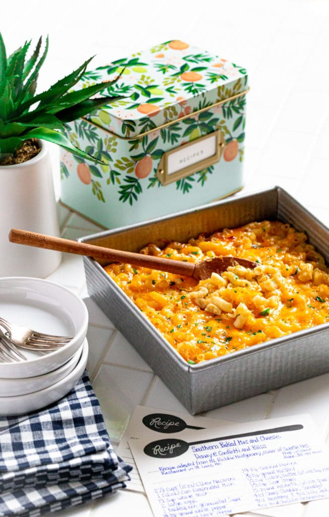 Baked mac and cheese in a square baker on a countertop next to a recipe box.