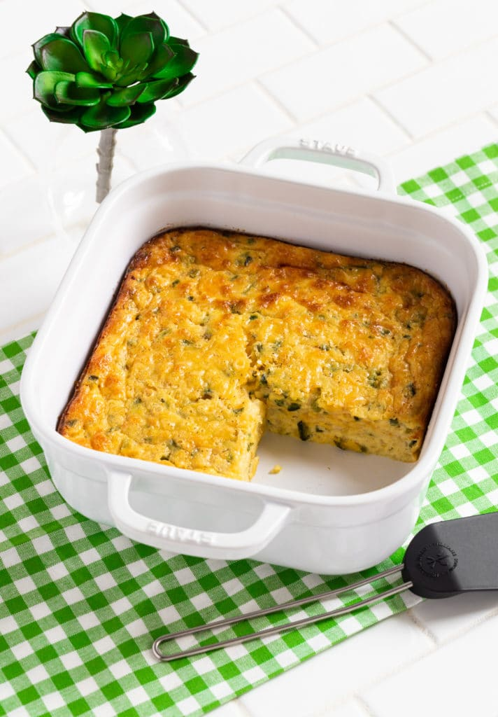 Chile relleno breakfast bake in a white square baker on a white tile countertop.