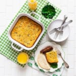 A chile relleno casserole breakfast bake on a white countertop with orange juice and sausages.
