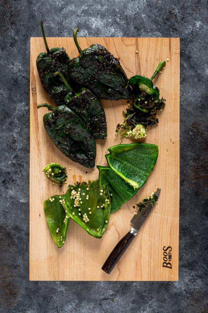 6 fire-roasted poblano peppers on a cutting board being prepped for a chile relleno casserole.
