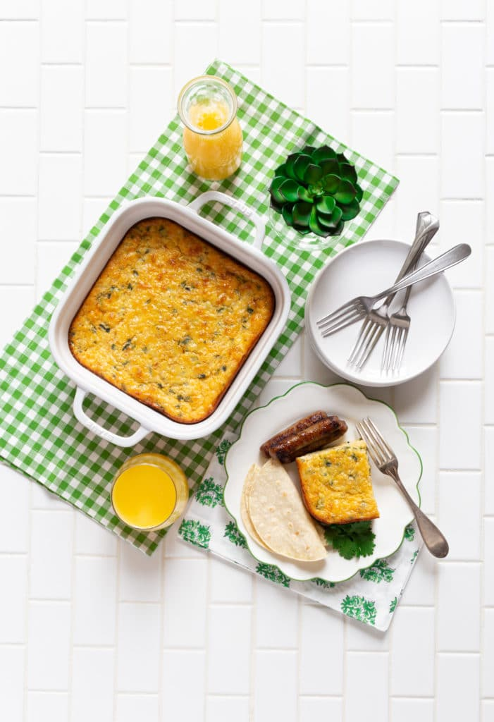 Chile relleno casserole in a white square baking dish on a breakfast table with orange juice.