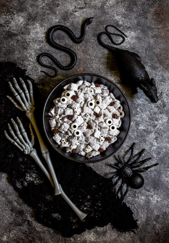 Halloween muddy buddies with candy eyes in a black bowl next to a rat, snake and spider.