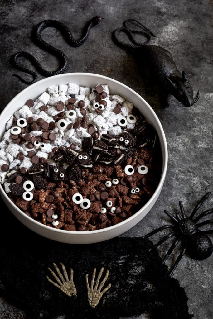 Halloween Muddy Buddies Chex Mix in a white serving bowl next to spooky Halloween decor.