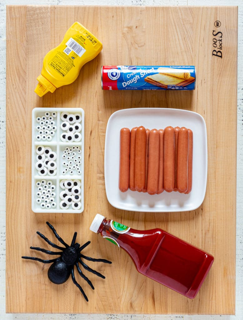 Ingredients for Halloween mummy hot dogs laid out on a wooden board.