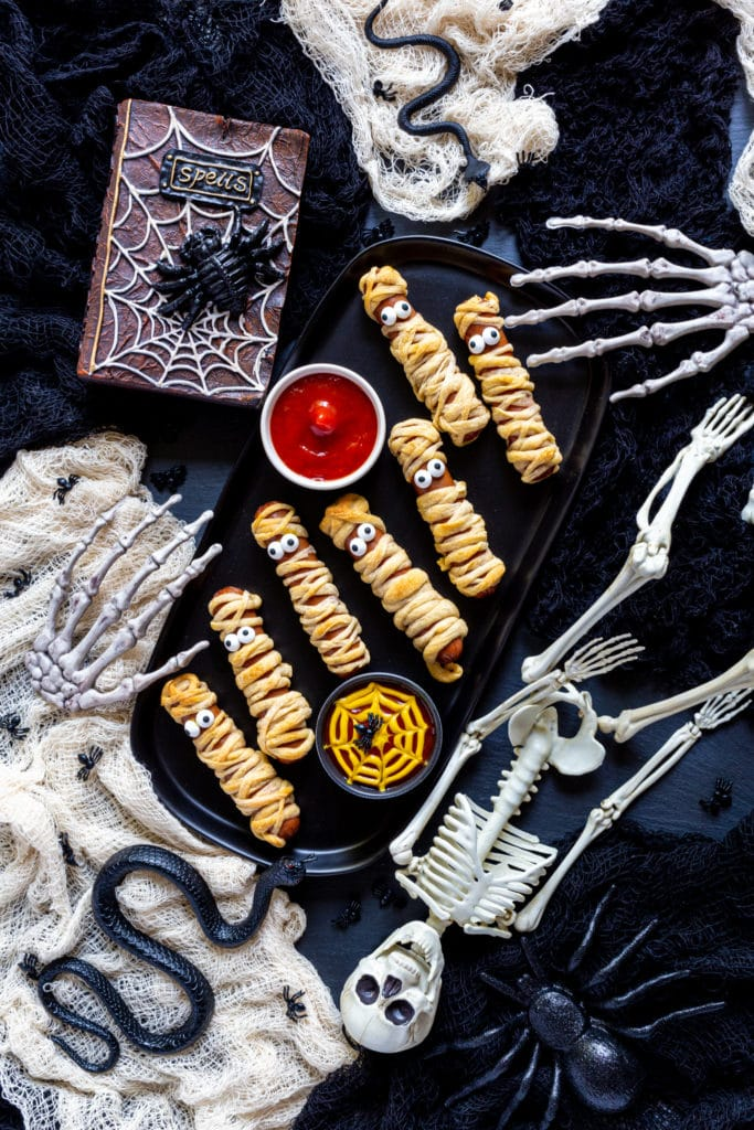 Mummy Hot Dogs on a black platter served with spider-web dipping sauce on Halloween table.