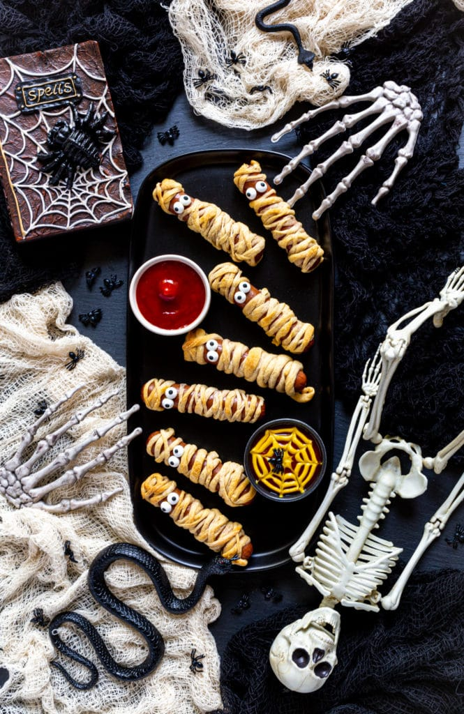 A platter of 6 mummy hot dogs on a spooky Halloween party table.