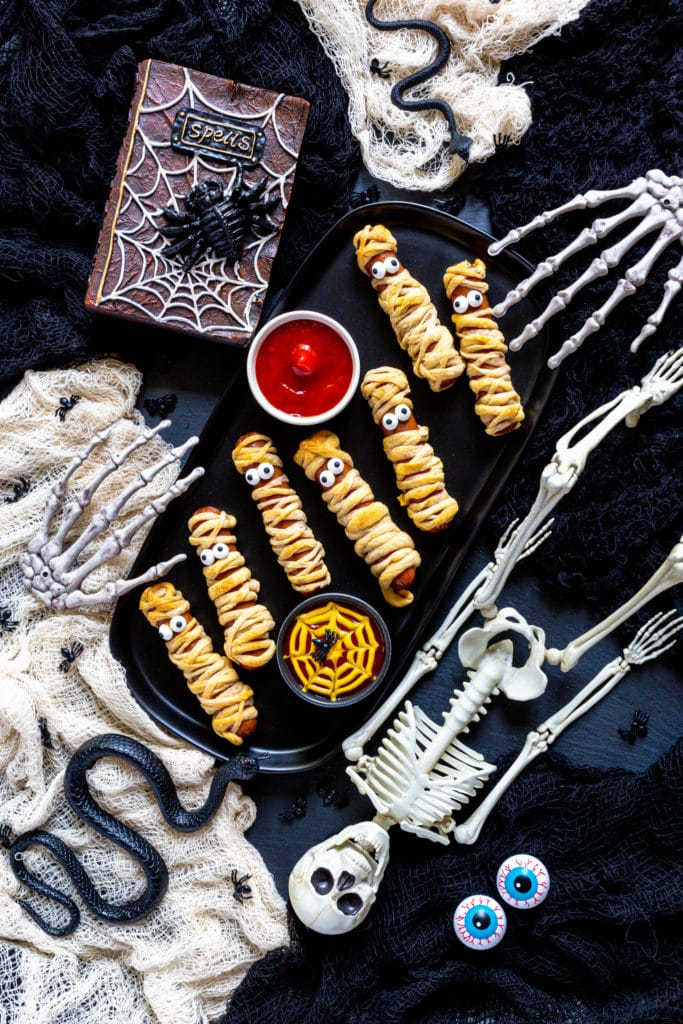 Hot Dog Fingers served on a black tray on a Halloween party table with spooky decor.