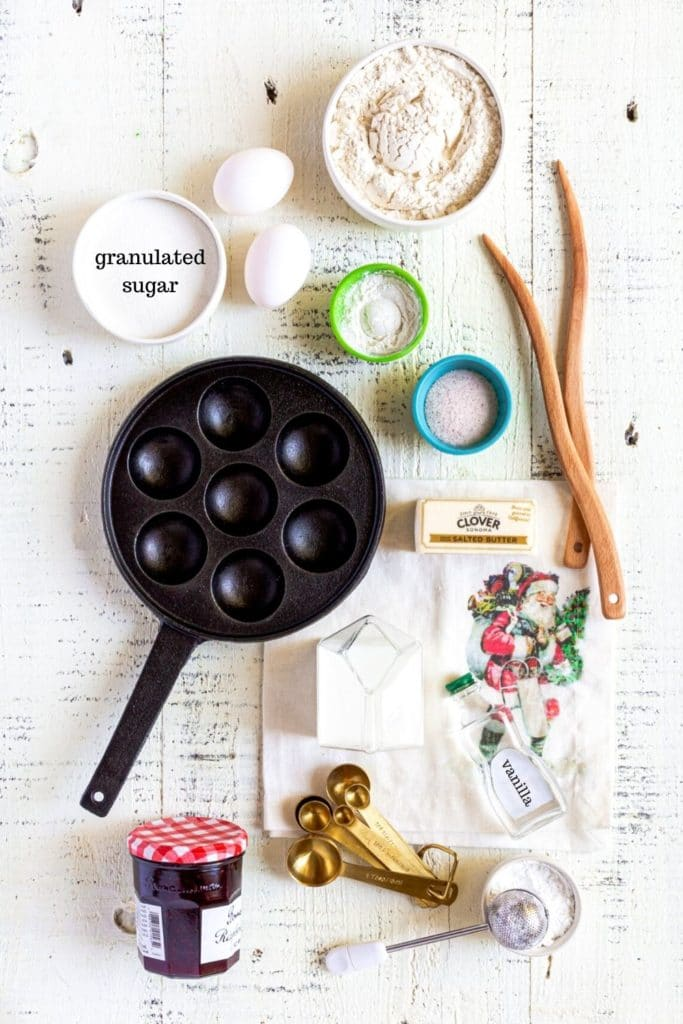 Ingredients for Aebleskiver Dutch Pancakes laid out on a white rustic tabletop along with cast-iron Ebelskiver pan and wooden turning tools.