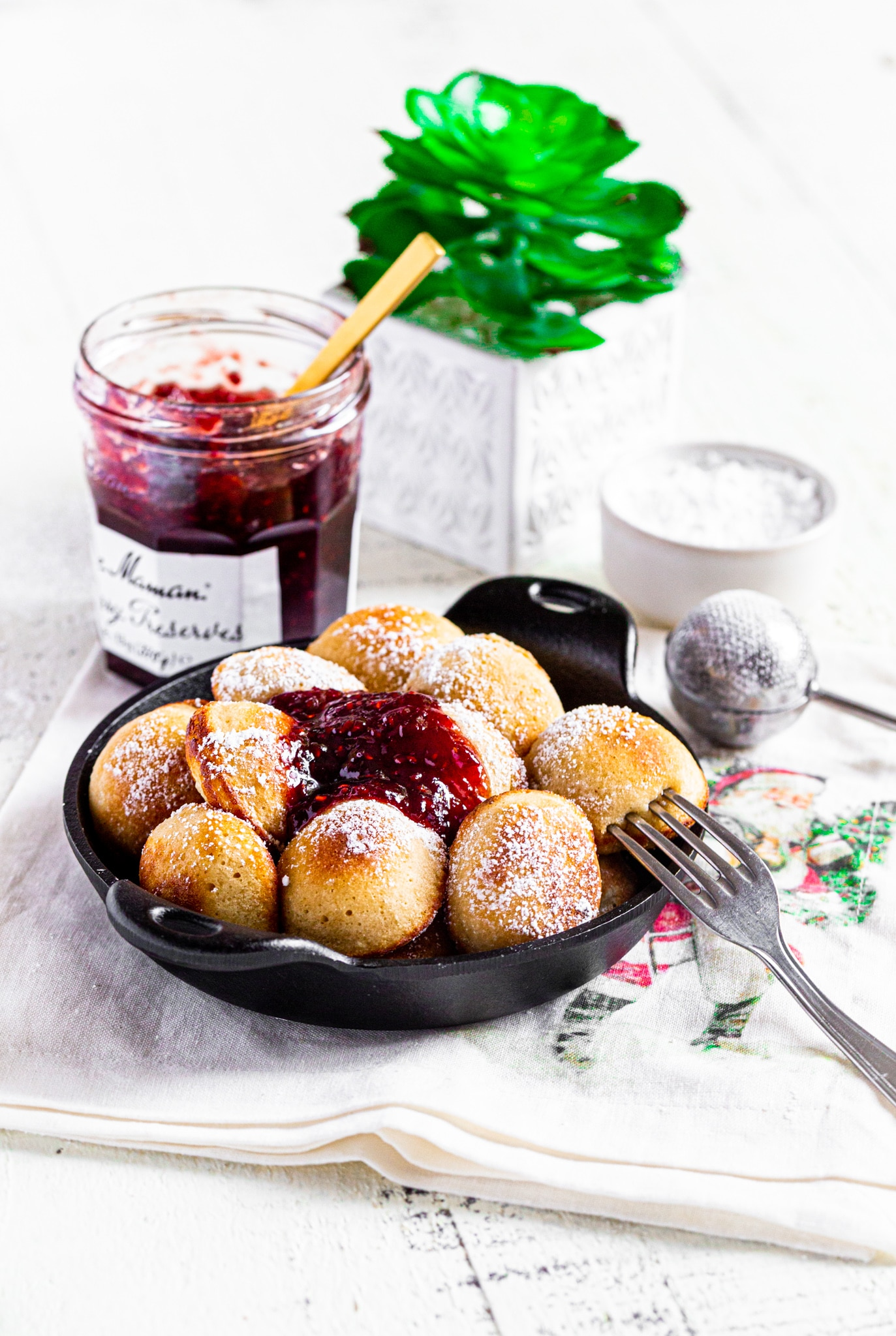 Aebelskiver mini pancakes with powdered sugar and raspberry jam in a mini round cast-iron server on a white tabletop with small plant.