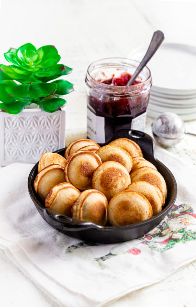 Danish aebleskiver mini pancakes in a round cast-iron dish next to a jar of raspberry jam.