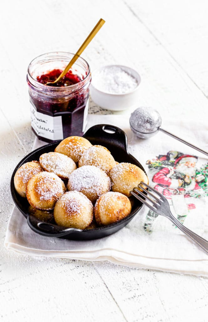 Small cast-iron dish with aebleskiver mini pancakes dusted with powdered sugar and jar of jam.