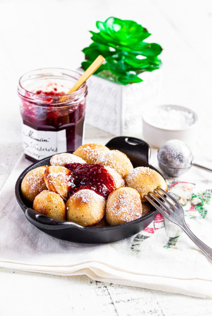 Aebelskiver mini pancakes with powdered sugar and raspberry jam in a mini round cast-iron server.