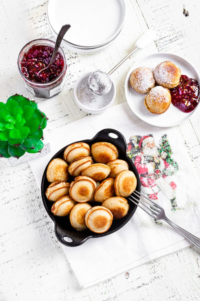 Overhead view of brunch table with Aebleskiver mini pancakes, jam, powdered sugar and small plant.