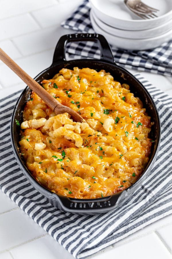 Southern baked macaroni and cheese served in an oval cast-iron gratin dish with wooden spoon.