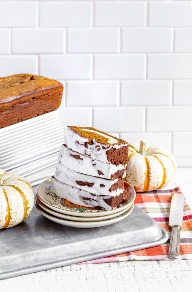 Four frosted slices of pumpkin cream cheese bread stacked vertically on a plate next to a pumpkin loaf.