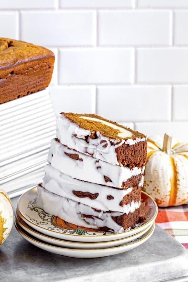 4 slices of frosted cream cheese bread on a stack of 3 dessert plates.