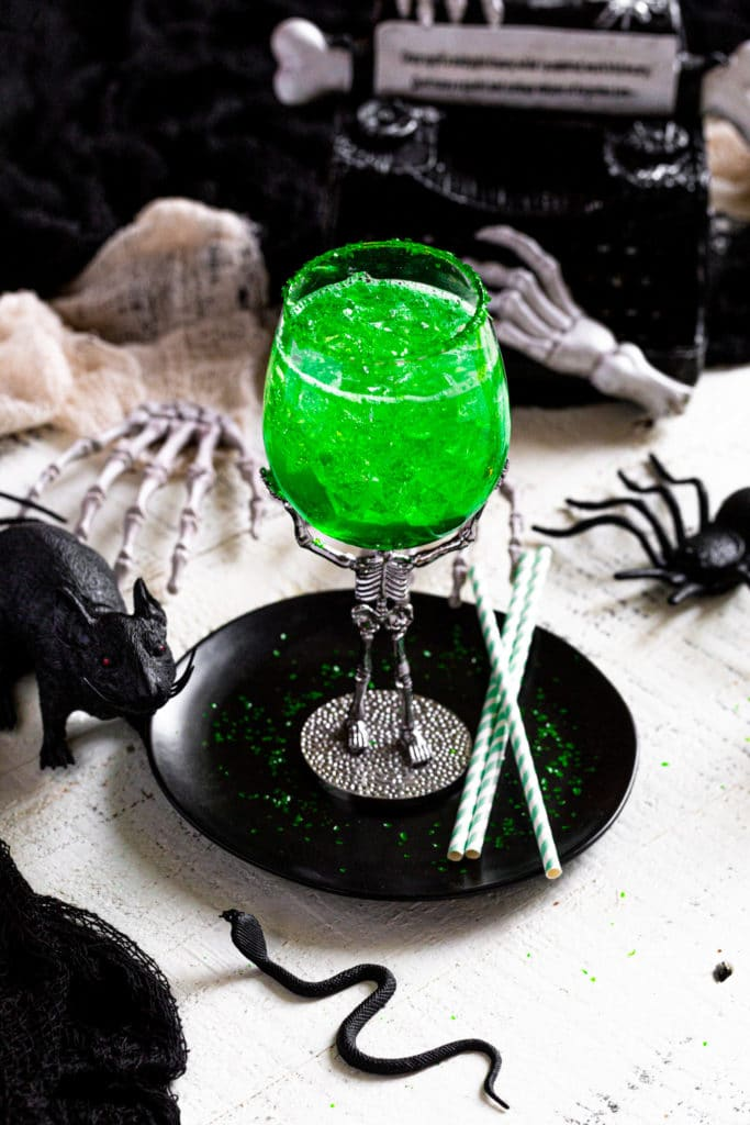 Spooky tequila cocktail served in a skeleton goblet for Halloween. The drink glows green.