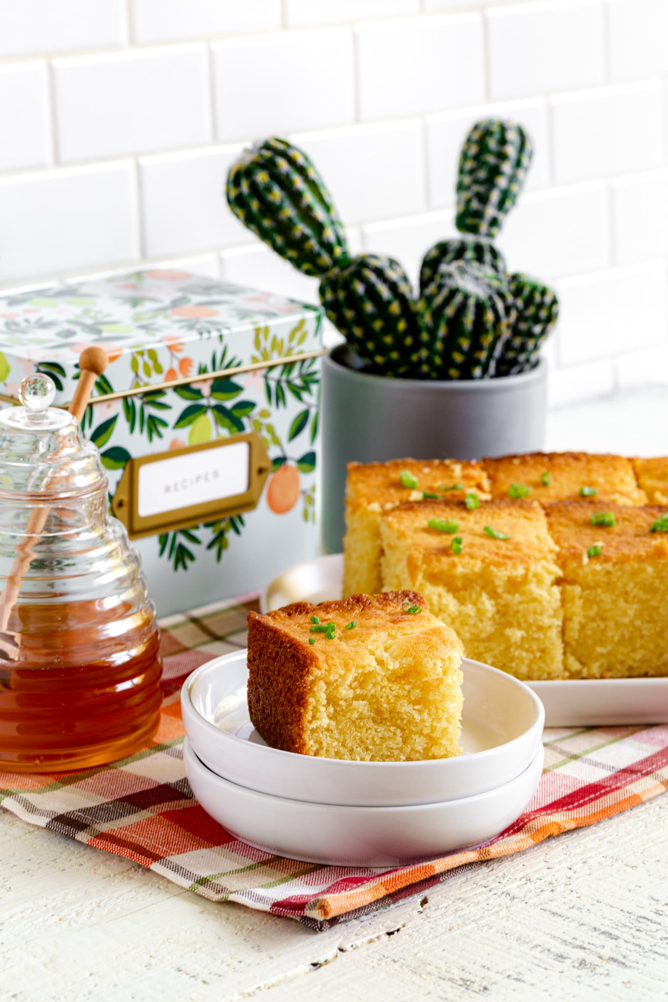 Serving of Jiffy cornbread on a white plate next to a platter of freshly-baked cornbread squares.