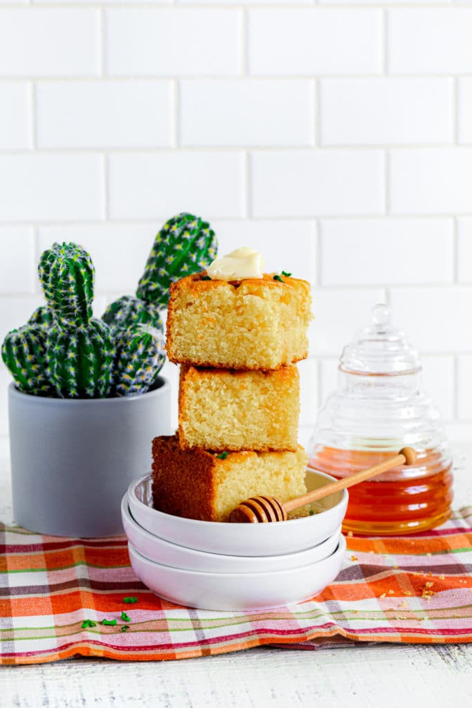 Stack of 3 cornbread squares on a stack of 3 small white plates with a wooden honey wand.