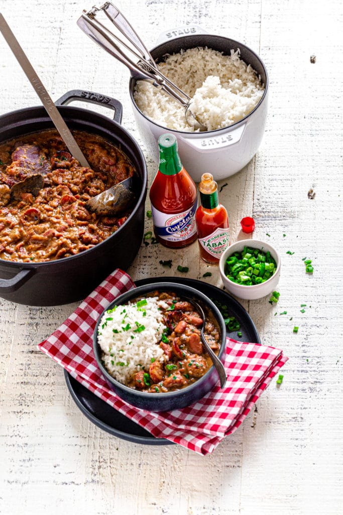 Red beans and rice served on a dinner table along with Louisiana hot sauce.