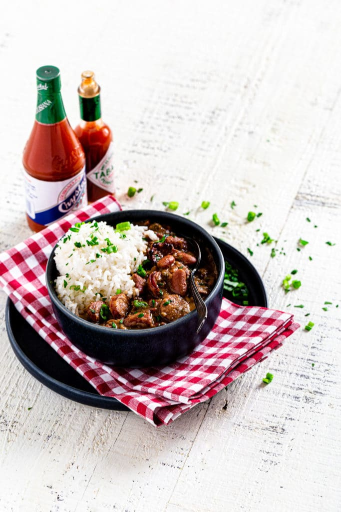 Serving of NOLA Red Beans and Rice in a blue bowl next to Louisiana hot sauce.