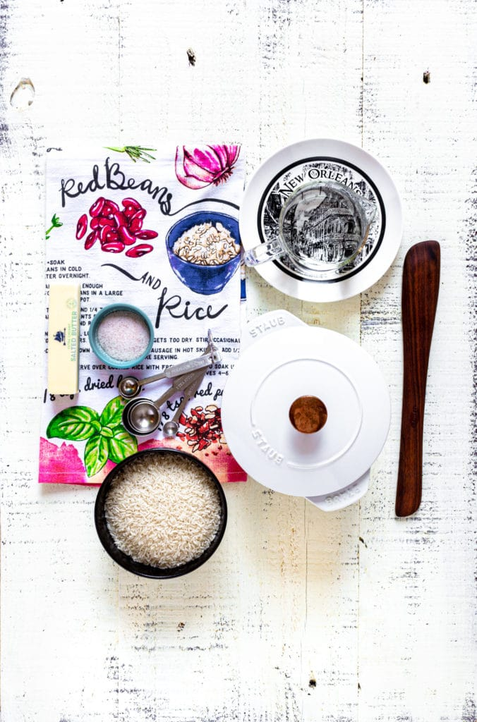 Ingredients for making white rice and a Staub cocotte on a rustic white tabletop.