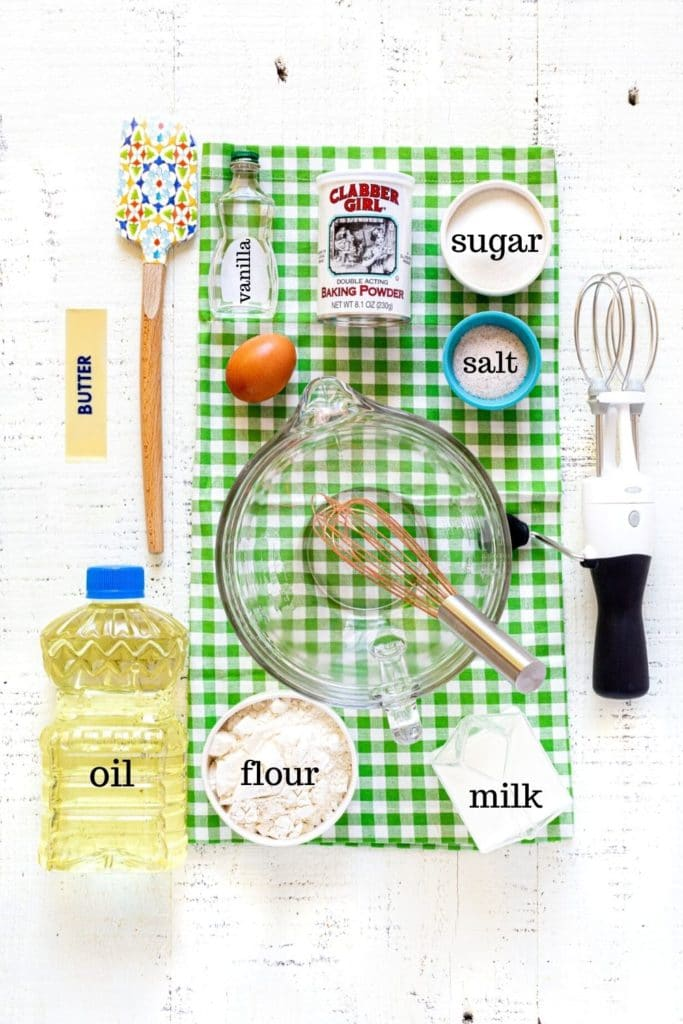 Ingredients for Belgian waffle recipe on a white tabletop with batter bowl, whisk and spatula.