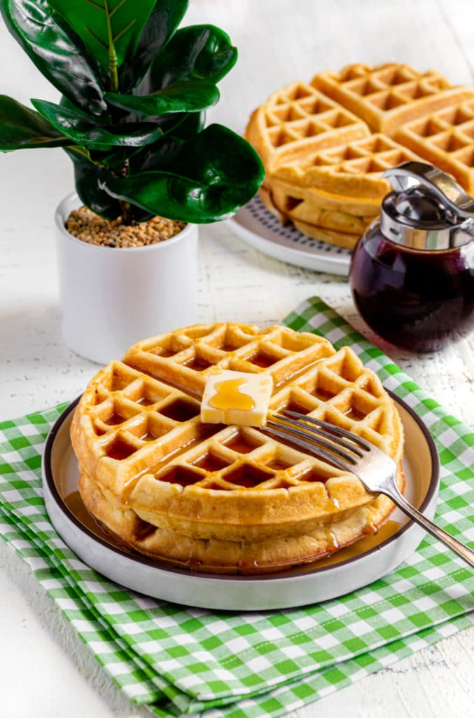 Plate of 2 homemade waffles with butter and syrup made with Grandma's Belgian waffle recipe.