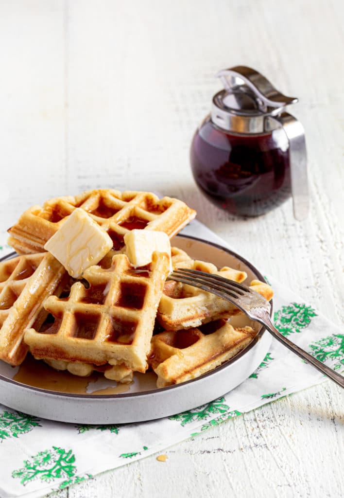 Belgian waffle divided into pieces, served on a plate with butter, maple syrup and a fork.