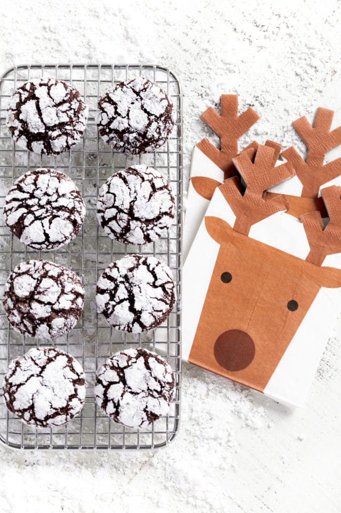 8 chocolate crinkle cookies (AKA crackle cookies) on a wire rack next to reindeer napkins.