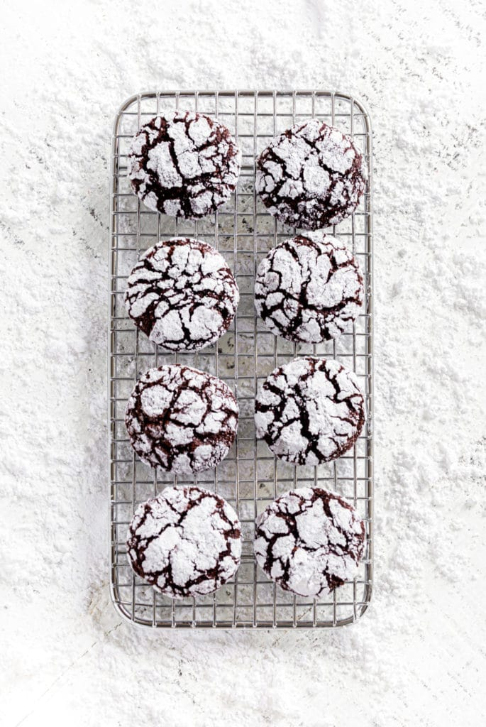 Overhead view of 8 chocolate crinkle cookies on a wire rack set on a white tabletop.