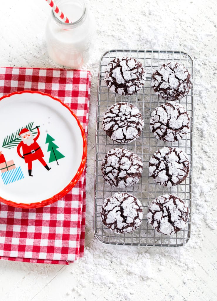 Chocolate Christmas Cookies (AKA Crinkles) on a wire rack next to small Santa plates and milk.