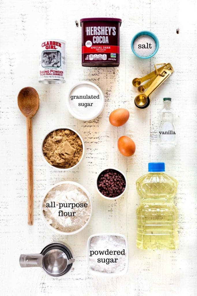 Overhead image of ingredients for chocolate crinkle cookies recipe laid out on a white rustic tabletop.