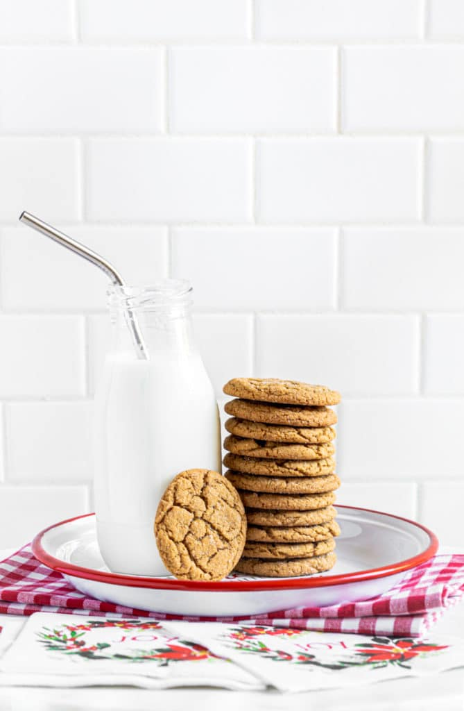 A stack of ginger snaps molasses cookies on a red-rimmed plate next to a bottle of milk with silver straw.