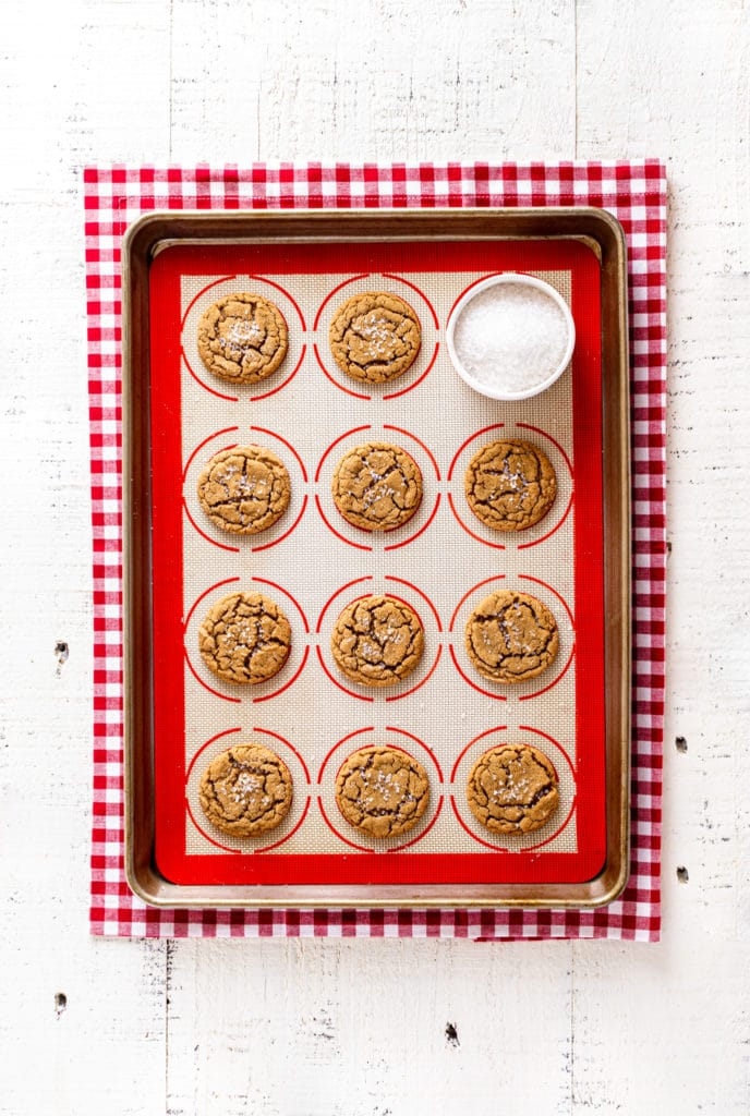 11 ginger snap cookies on a USA pan baking tray with silicone mat, and a ramekin of sparkling coarse sugar crystals.