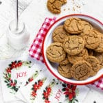 Overhead view of a plate of ginger snap cookies with milk and holiday napkins.
