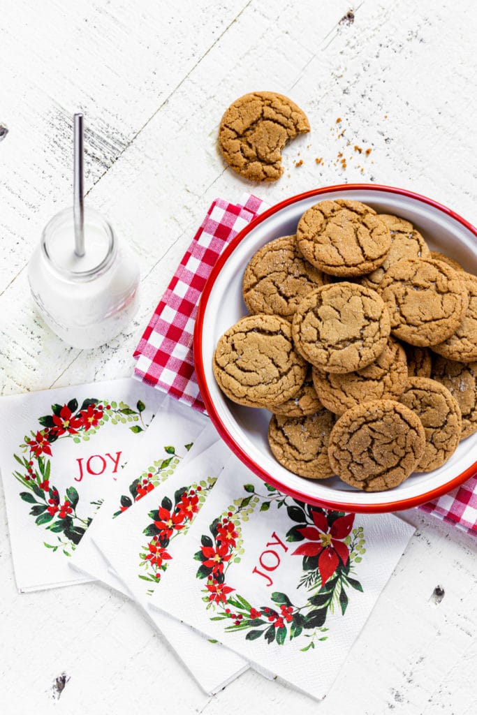 Ginger snap cookies on a plate with glass bottle of milk with straw and holiday napkins.