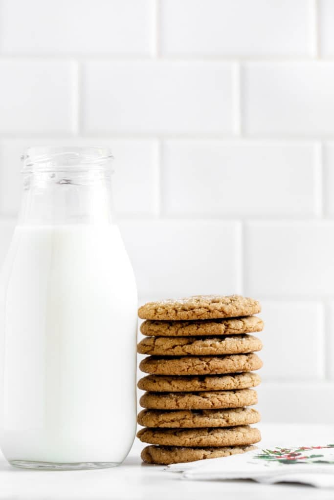 Stack of 8 ginger snap cookies next to a glass bottle of milk and holiday napkins.