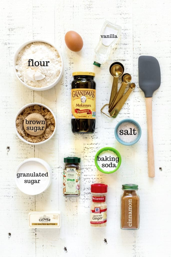 Ingredients for gingersnap cookie recipe laid out on a white farmhouse tabletop with gold measuring spoons and spatula.