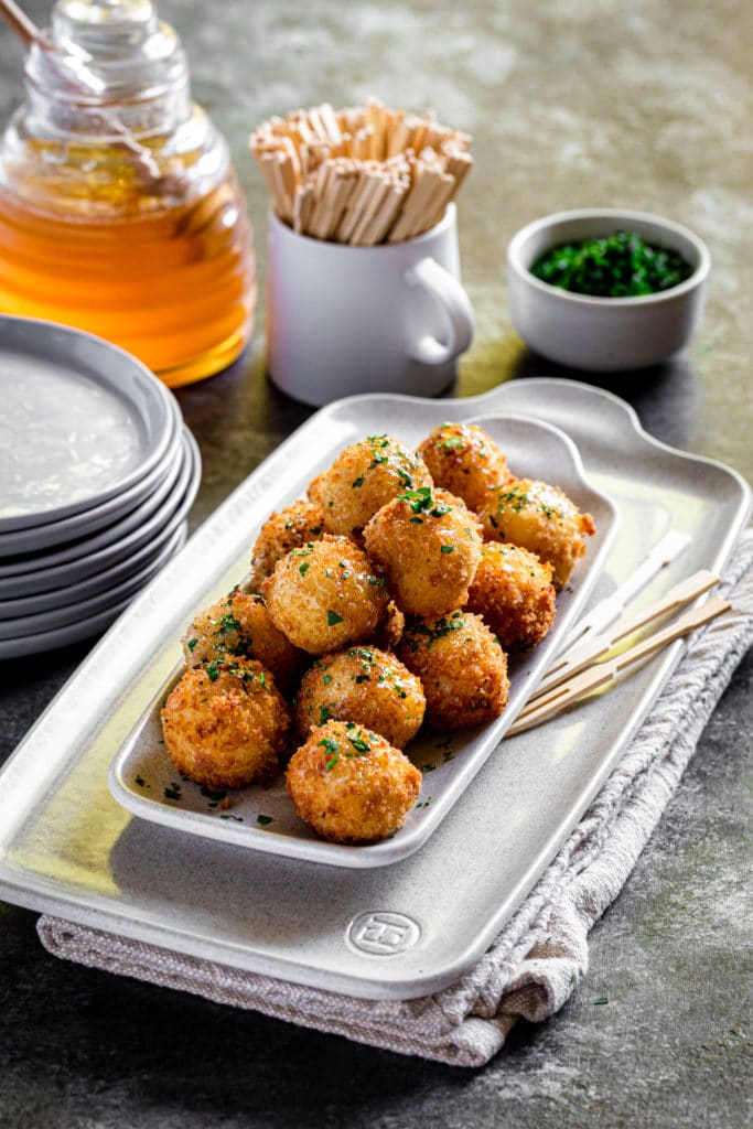 Honey goat cheese balls tapas on stacked appetizer plates on a grey tabletop.
