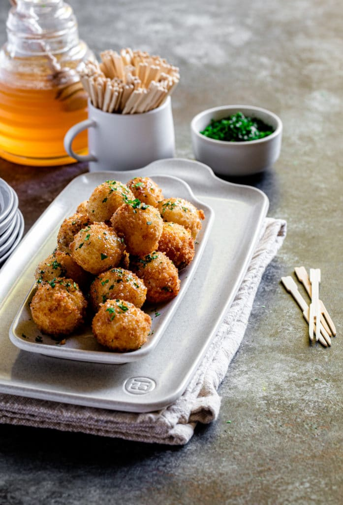 Small tapas plate with honey goat cheese balls and parsley on a smokey grey tabletop.