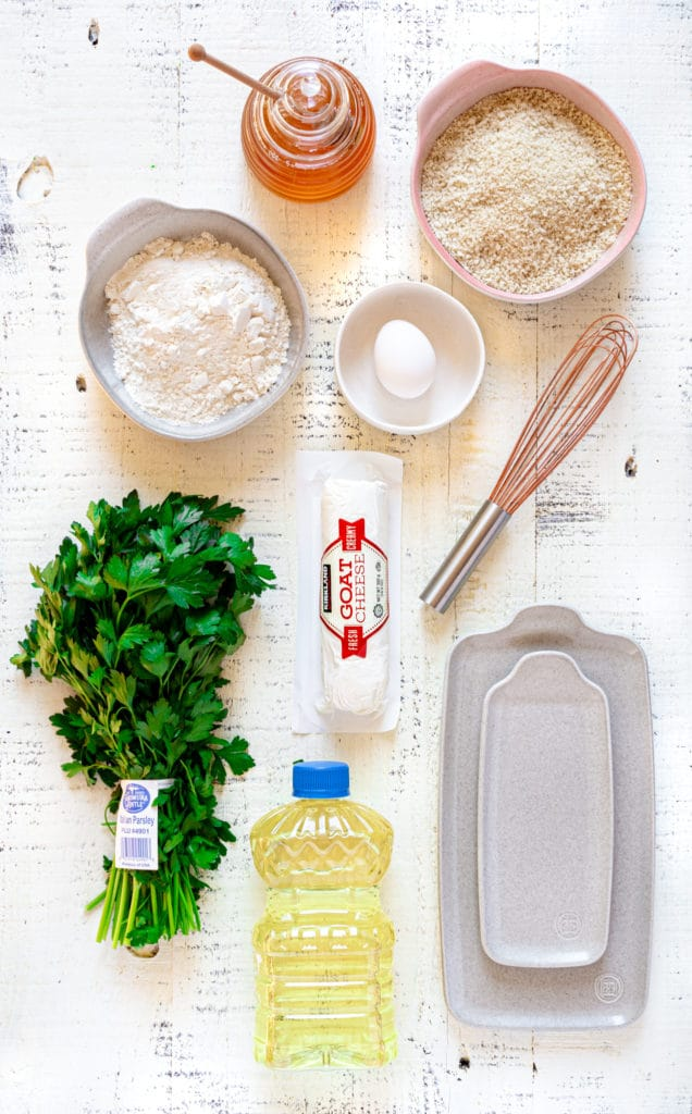 Ingredients for making fried goat cheese balls laid out on a rustic white tabletop.