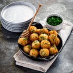 Fried honey goat cheese balls in a small round cast-iron dish next to a stack of appetizer plates.