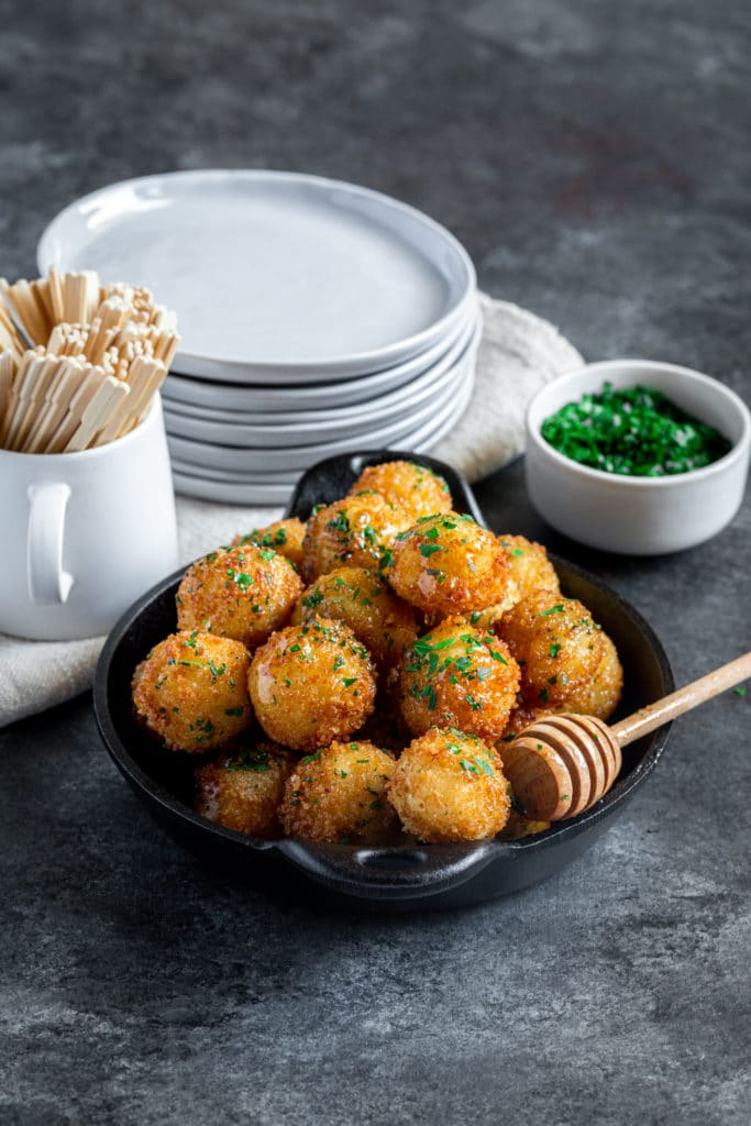 Honey Goat Cheese Balls sprinkled with parsley, served in a tapas dish with wooden honey wand.