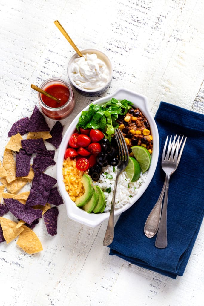 Healthy burrito bowl in a white oval dish with fork, navy blue napkin, and tortilla chips.