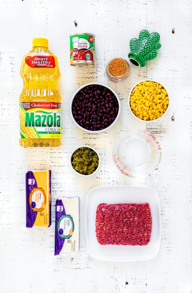 Ingredients for making a healthy burrito bowl laid out on a white rustic tabletop.