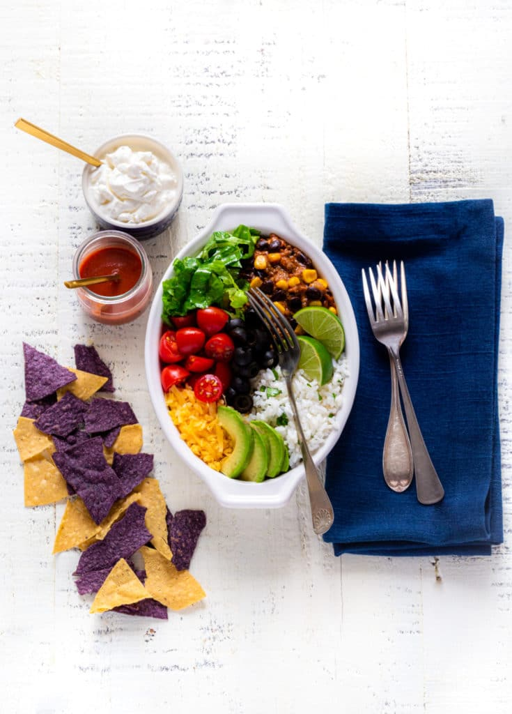 Burrito bowl recipe served in oblong bowl with lime wedges, chips, sour cream and hot sauce.